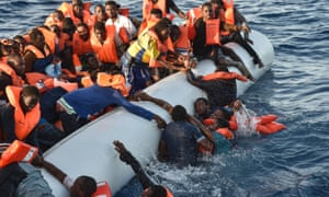 Migrants and refugees panic as they fall in the water during a rescue operation in the Mediterranean