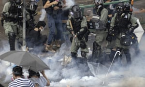 Riot police detain protesters amid clouds of tear gas at Polytechnic University.