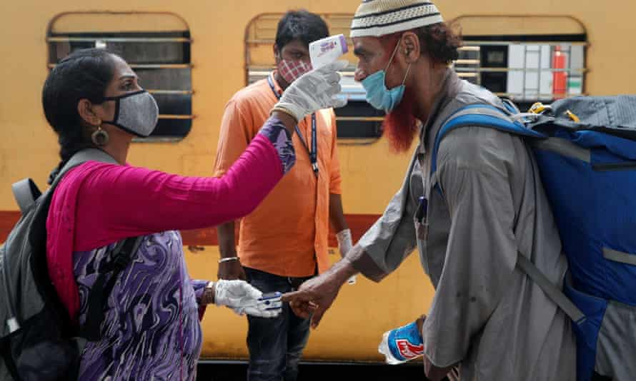 A health worker checks a passenger's temperature and pulse at a railway station in Mumbai