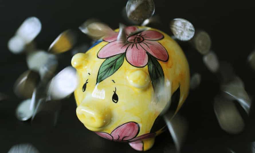coins spilling over a yellow piggy bank