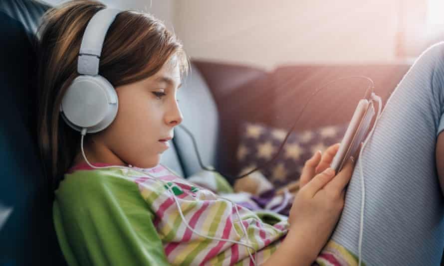 Girl sitting on black sofa using tablet.