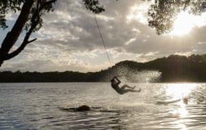 A young man swings from a tree into Lake Ainsworth in Lennox Head, Australia