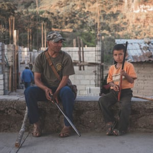 Mexico; Guerrero; Ayahualtempa; 2020 Member of the indigenous community police CRC-PF, with a child who's joining the self-defence group in response to criminal group violence.