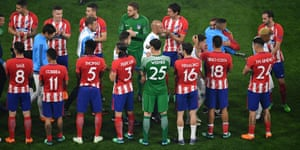 Atletico Madrid players give a guard of honour to Marseille players.