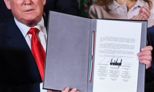 Donald Trump holds copy of trade agreement