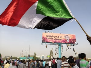 Sudanese anti-regime protesters wave a flag above a billboard with an image of Alaa Salah