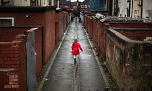 A child plays in the alleyways of Manchester