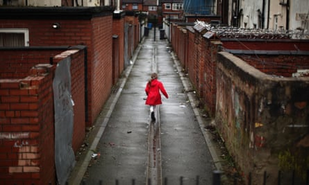 A girl plays in an alleyway in Gorton, Manchester