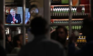 Customers at the Westminster Arms, near the House of Commons watch on as Boris Johnson gives his televised address on the latest coronavirus restrictions.
