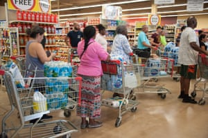 People queue for supplies at a Winn Dixie store in South Florida.