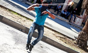 A Palestinian youth throws a stone with a slingshot at the northern entrance to Hebron.