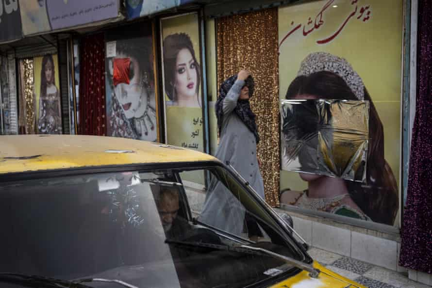 A woman walks past beauty salons with window decorations which have been defaced in Kabul, Afghanistan