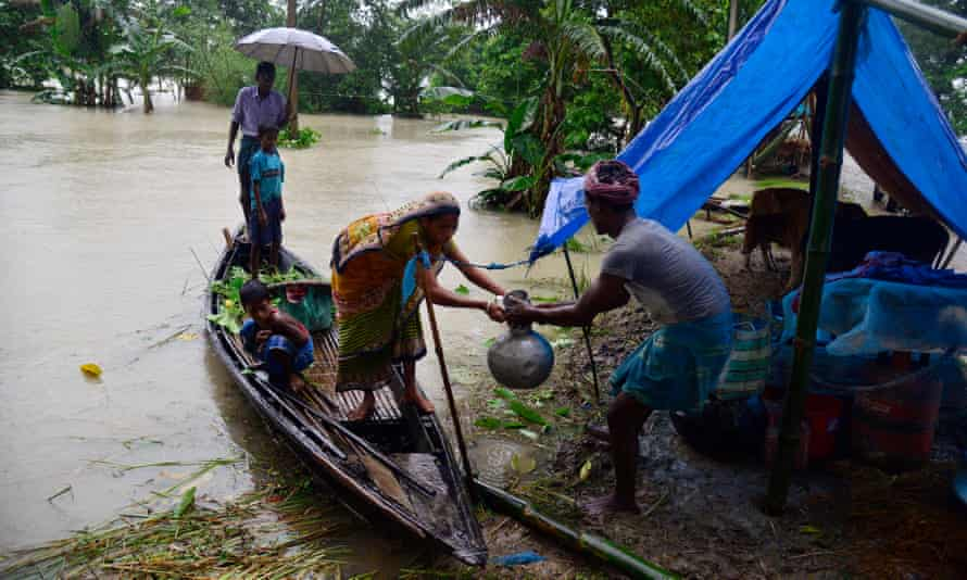 A family bring their belongings to a makeshift camp in Morigaon district of Assam