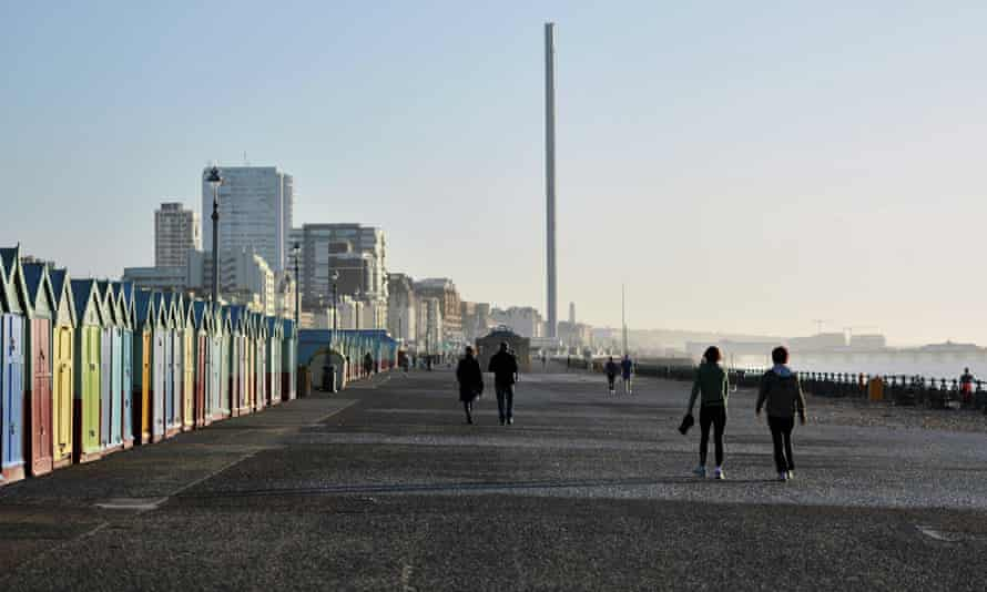 Walkers enjoy the mild early December weather at the seafront in Hove, Sussex.