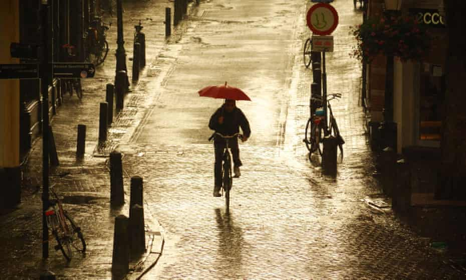 A cyclist rides in the rain in Utrecht, where 60% of city centre journeys are made by bike.