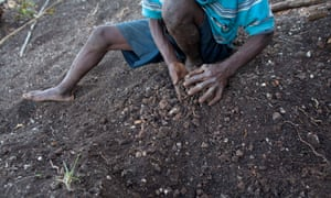 Farmer Jean Romain Beltinor works the rocky dirt on his parched hillside in 2014 to prepare for planting seeds in northwestern Haiti after months of drought.