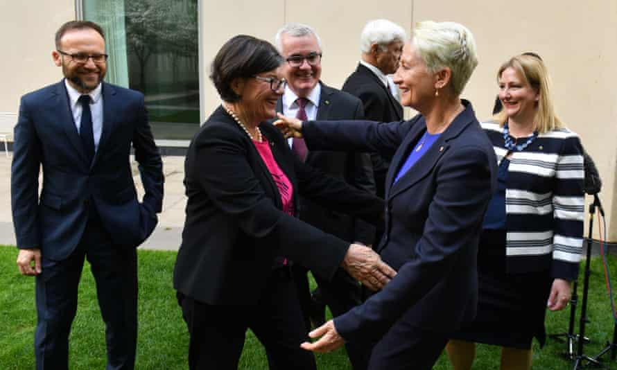 Independent member for Indi Cathy McGowan (second from left) and independent member for Wentworth Kerryn Phelps hug as Greens Member for Melbourne Adam Bandt (left), independent member for Denison Andrew Wilkie, Bob Katter and Centre Alliance member for Mayo Rebekha Sharkie look on.