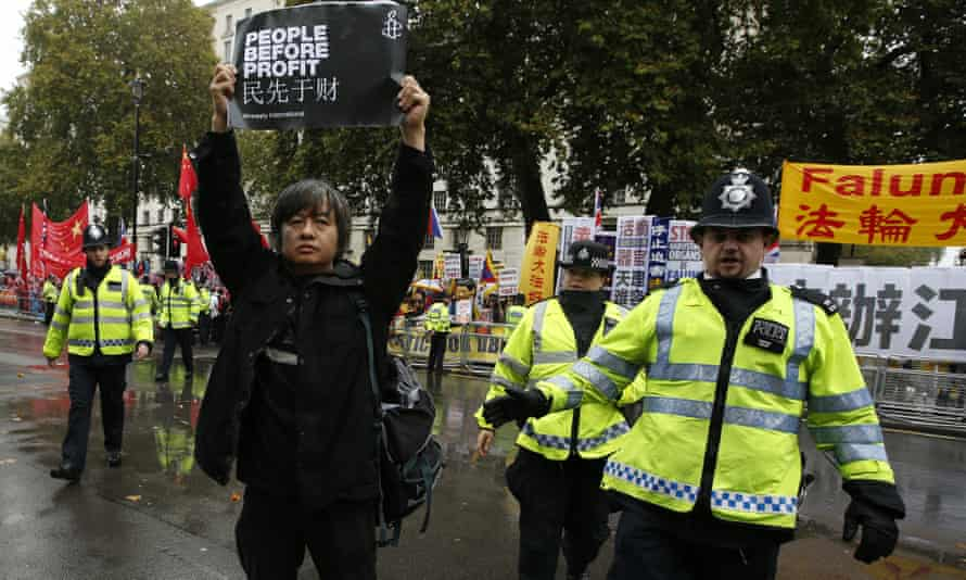 A protester is moved on by police as he takes part in a demonstration against the visit of Xi Jinping.