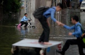 Rawalpindi, Pakistan A student helps a friend on to a waste container upended on a flooded street after heavy monsoon rains