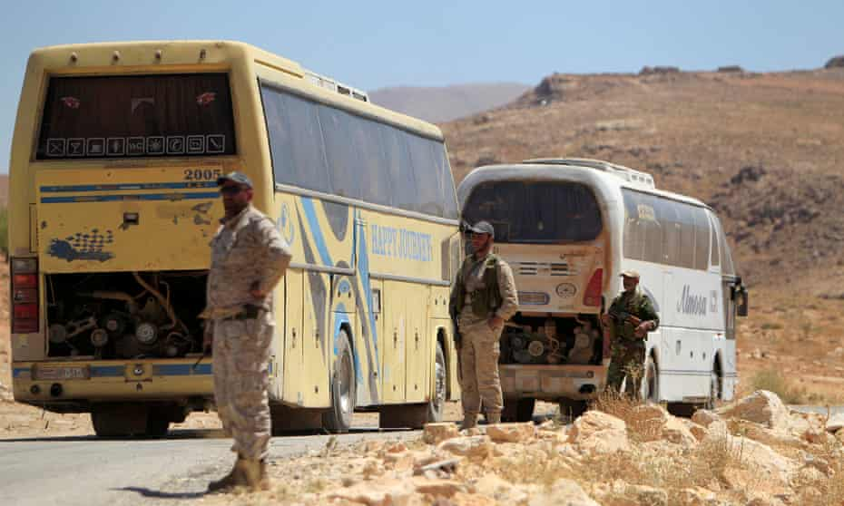 Hezbollah fighters stand near buses in Jroud Arsal, near Syria-Lebanon border.