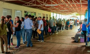 Nicaraguans queue at a migration office in Managua, to obtain their passports on Wednesday. Many Nicaraguans are seeking to migrate to Central American border countries, escaping a two-month long uprising.