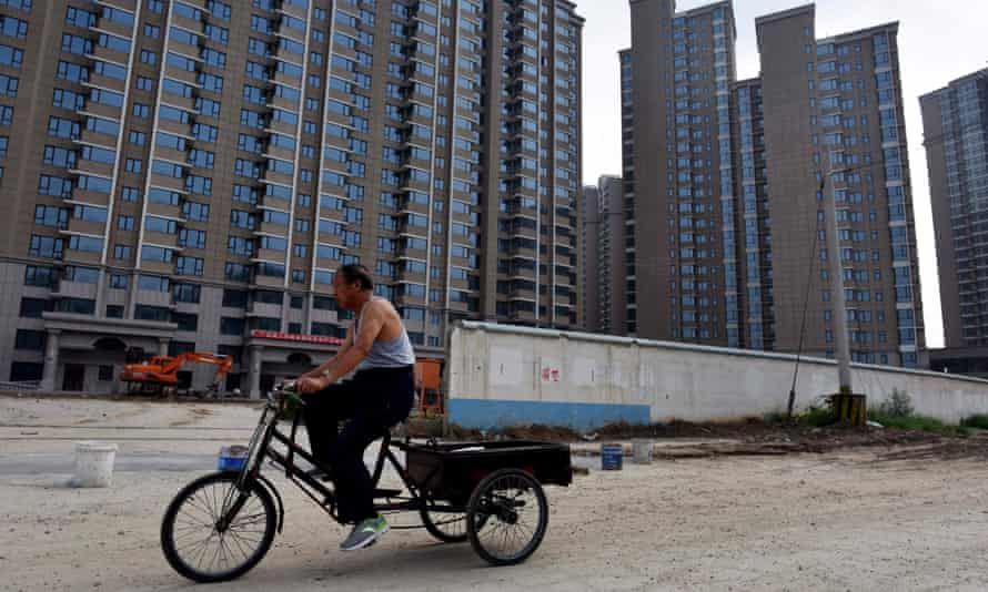 A man cycles past the construction site of a housing complex in Beijing