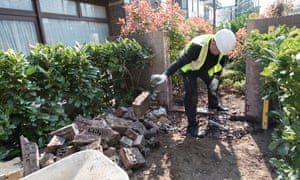Henley Homes workmen remove the wall at Baylis Old School development in Lambeth, London, which excluded children of social housing from using the shared playground, following a Guardian Cities investigation.
