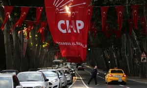 A man crosses a street under the flag of Turkey's main opposition Republican People's party (CHP), in Istanbul.