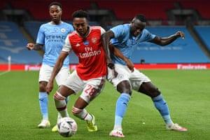 Arsenal's Joe Willock (centre) tangles with Manchester City's Benjamin Mendy.
