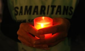 A Samaritans volunteer holding a candle