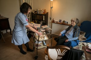 Claire Routh, a community nurse, checks a patient's tblood sugar levels and gives an insulin injection