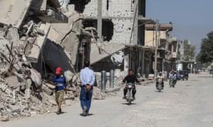 People walk past destroyed buildings in the town of Kobani.