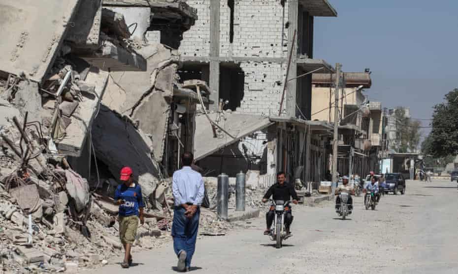 People walk past destroyed buildings in Kobane in June 2015