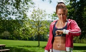 Portrait of a woman in sportswear checking an Apple Watch Sport