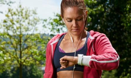 A woman checks her fitness tracker after a run