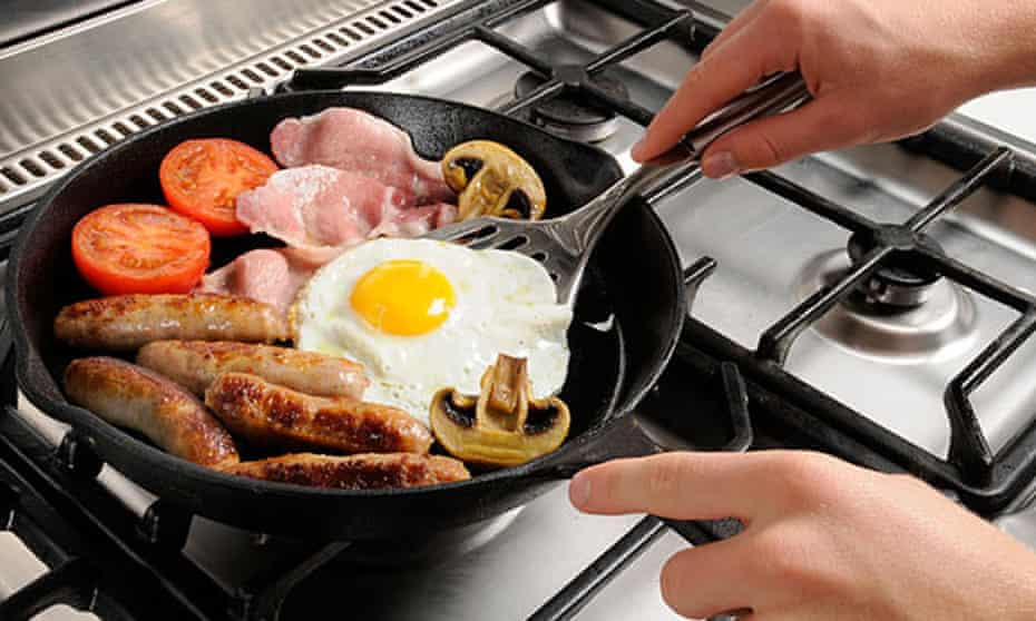 Someone cooks a fried breakfast