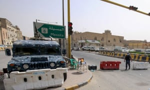 Kuwaiti police officers man a checkpoint at the entrance to the town of Jeleeb Al-Shuyoukh