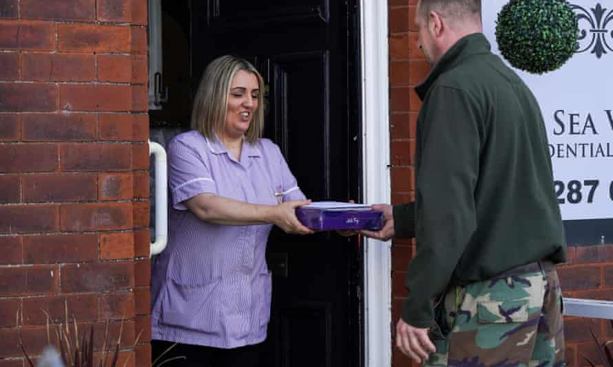 A care home worker takes a Mother's Day gift for a resident in Saltburn-by-the-Sea, North Yorkshire.