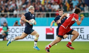 Darcy Graham of Scotland runs with the ball before passing it to George Horne of Scotland who goes on to score his team's fourth try
