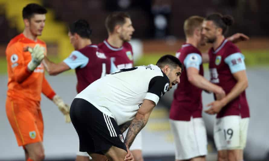 Aleksandar Mitrovic contemplates Fulham's relegation from the Premier League as Burnley's players celebrate their survival.