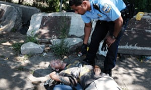 A police officer tries to revive a man who overdosed on heroin in the Kensington section of Philadelphia.