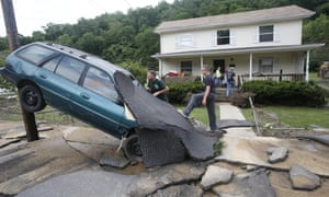 Jay Bennett, left, and step-son Easton Phillips survey the damage to a neighbor's car in front of their home in White Sulphur Springs, West Virginia.
