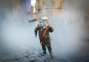 People dressed in mock military attire throw eggs as they take part in the traditional Els Enfarinats battle in the Spanish town of Ibi.