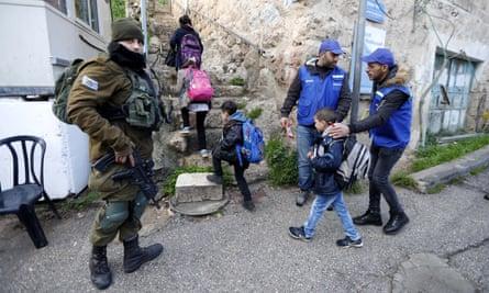 An armed Israeli soldier looks on as Palestinians wearing blue uniforms escort schoolchildren in the West Bank city of Hebron.