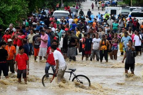 People wait for help on a flooded main roadin La Lima, Honduras