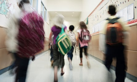 Young students walking down hallway of school<br>Young students with backpacks walking down hallway of elementary school