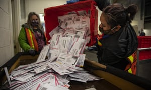 Election worker Kristen Mun empties ballots from a ballot box at the Multnomah county elections division in Portland.