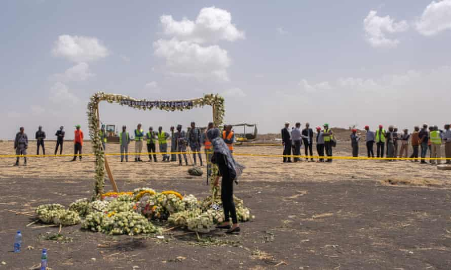 A mourner lays flowers at the memorial march during a visit to the crash site of Ethiopian airlines flight ET302 on 14 March in Ejere, Ethiopia.