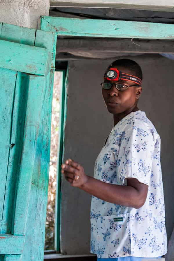Marie Lerrecile Charles wears a headlamp to perform gynecological exams at a rural mobile clinic.