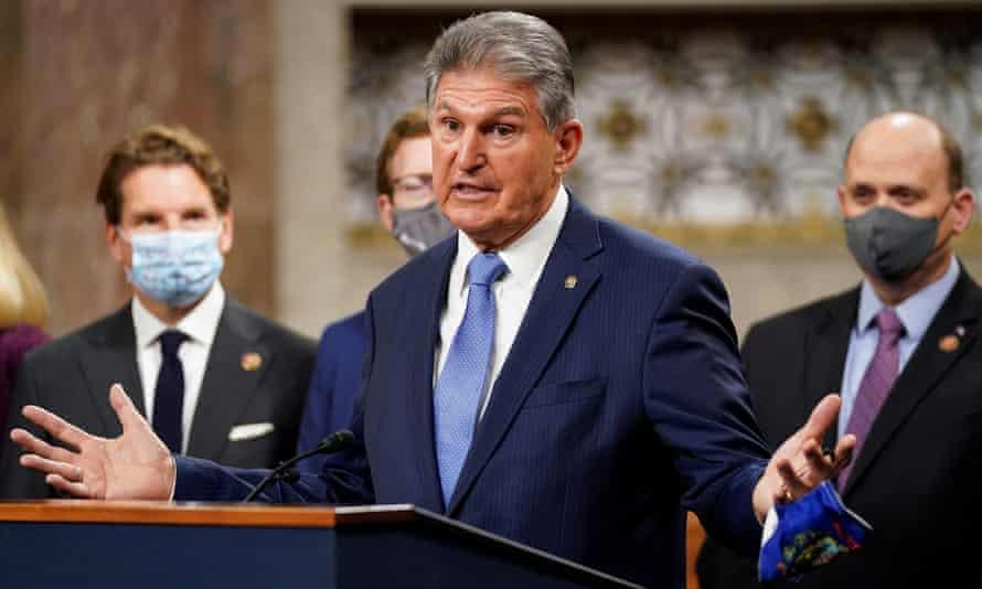 Senator Joe Manchin removes his mask to speak.